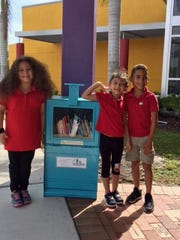 "Students at Harlem Heights Community Charter School pose for a photo with their Little Free Library, which was provided and maintained by the ""And Literacy for All"" nonprofit."