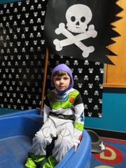 Buzz Lightyear, a.k.a.  Liam Mikulec, 3, of Milford, takes a break in a make-shift pirate ship at the Treasure Trove of Fun Halloween party.