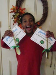 Josiah Carpenter proudly displays his Golden Spoon awards. Josiah entered the 4-H Holiday Bake Off in the bread and healthy choices categories.