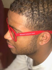 "Gerrard Taylor, who attends Tap Into Life young adult programs at the Father Solanus Center is wearing red glasses with ""Blessed Solanus Casey"" on the side that are inspired by the red-rimmed glasses Casey wore when the Capuchin friar ministered at St. Bonaventure Monastery in Detroit.  Some glasses will be part of a giveaway Saturday directed at young people attending the beatification ceremony at Ford Field of Blessed Solanus. Some handheld fans with an emoji-like image of the Capuchin friar also will be distributed."