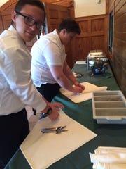 Ayden Jeffery (left) and Brannon Houck roll silverware ahead of their hospitality class luncheon at Golden Mast in Okauchee.