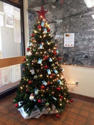 """The """"Make a Child Smile"""" Christmas Tree is set  up in the front end of the John Strand Municipal Building located at 309 S. Gold Street. The public is invited to select a tag from the tree and provide gifts for the child listed on the tag."""