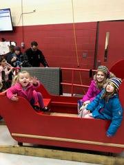 "Gracie Davies, Mariella Hartman and Ansleigh Hartman climb into a sleigh at Farmington Hills holiday ""Lights"" ceremony."