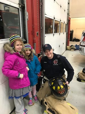 Mariella Hartman, 8, and Ansleigh Hartman, 6, with Farmington Hills Firefighter Colin Brennan.
