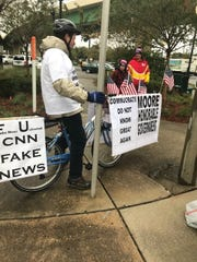 "Peter Grove of Cloverdale, Alabama, rode his bike around the Civic Center in the rain. His bike was adorned with signs in support of Roy Moore and denouncing CNN as ""fake news."""