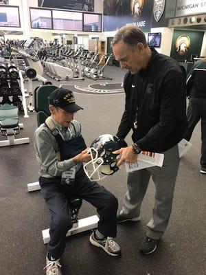 Michigan State head football coach Mark Dantonio hands an autographed helmet to 53-year season ticket holder, Howard Grider, 92, Sunday inside the Duffy Daugherty Building.