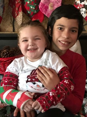Noel Somoza holds his nearly 6-year-old sister Cierra for a Christmas picture.