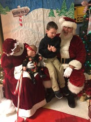 Students Adalynn and Owen B. of The Learning Experience taking photos with Mr. and Mrs. Santa Claus.