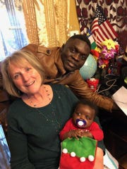 MAC volunteer Lorraine Engel holds three-month-old Angel Kagde as his father Placide stands in front of the family's first Christmas tree. They are from the Central African Republic.