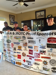 Officers of the Treasure Coast chapter of the Military Officers Association of America Bobbie Williams, left, Dayne Clemmer, Sally Clemmer and Bill Armstrong hold the banner of sponsors and donors for the Feb. 3 5K walk/run in Tradition.