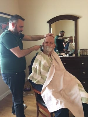 """Lenny White, """"the dementia friendly barber"""" provides a shave for Lyle Leeson, a resident of Brightview Randolph."""