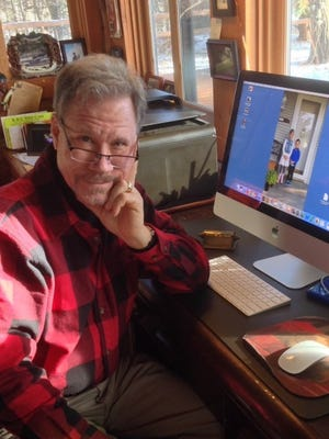 """Douglas Wood in his Pine Point cabin by his """"friend,"""" the computer."""