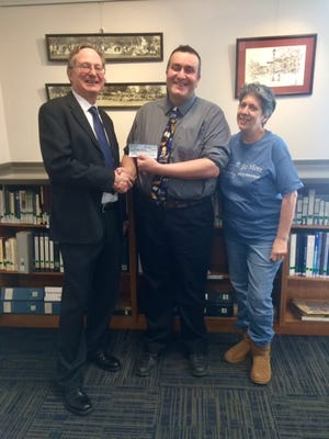 Clarkson Town Supervisor Jerry Underwood made a campaign promise that if he won he would donate his salary and he did. He wrote a check for $18,000 to the Seymour Library. Here he hands the check to Seymour Library Director Carl Gouveia and library board president Taysie Pennington.