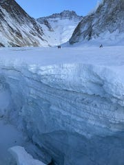Members of McLeland's climbing party across a great ice crevasse on Mt. Everest.