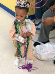 Kinsley Cormier, 18 months, shows off her tiara and bead collection during the sixth annual Mardi Gras parade at Women's & Children's Hospital Friday, Feb. 9, 2018.