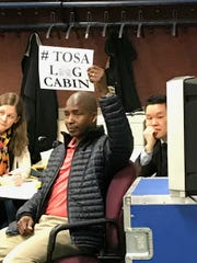 Wauwatosa Alex Joseph holds up a sign in support of saving the log cabin during the Common Council meeting on Feb. 20. A apartment project may raze the cabin if the proposal is approved.