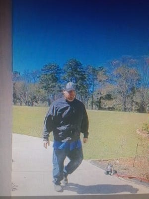 Surveillance photo of a man believed to be a suspect in the theft of commercially delivered packages.