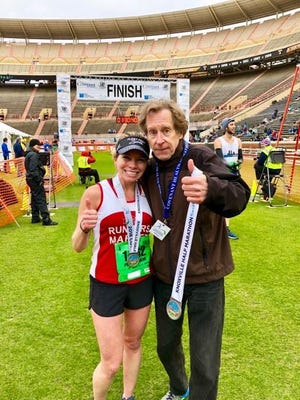 Andee Swann, left, poses with running legend Bill Rodgers at Neyland Stadium, after finishing second in the women's half marathon Sunday.