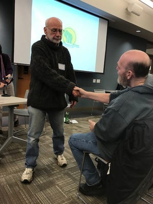 An audience member shakes the hand of Carl Lindner after he spoke during the listening session hosted by the Clean Power Coalition on April 4 at the Oak Creek Public Library regarding coal dust.