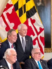 Delegate Charles Otto, R-38A-Somerset, standing at left, and Sen. James Mathias, D-38, standing right, pose with Senate President Mike Miller, seated at left, and Gov. Larry Hogan after Hogan signed a bill that allows golf carts to be driven on Crisfield streets on Tuesday, April 10, in Annapolis.