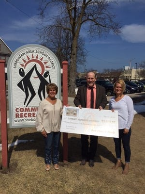 Barb Kleine and family (pictured with Recreation Department's John Koehler) donated $3,500 in memory of her husband. With this donation, all three Field of Dreams baseball/softball field scoreboards will be installed in May.