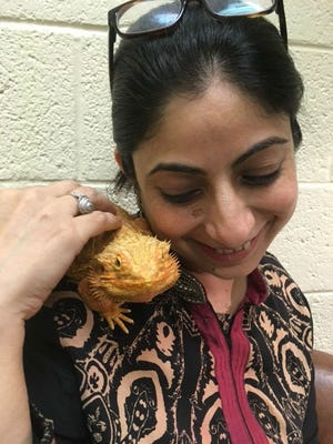 Dr. Deepa Katyal, a practicing veterinarian from Mumbai, with a bearded dragon that lives at the shelter Humane Society of Vero Beach and Indian River County.