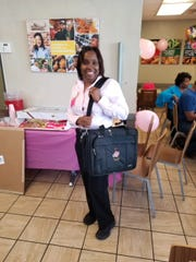 """Diane Liddell poses with a bag that was a gift from Church's Chicken at a party celebrating her 40th anniversary at the fast-food franchise. Liddell grew up in Utica as one of 10 brothers and four sisters, and occasionally picked cotton with her father and older siblings. After picking cotton, Church's was """"a breeze,"""" she said."""