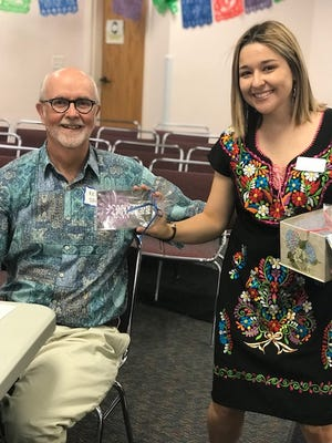 Literacy Services of Indian River County Tutor Trainer Anali Vierya, right, shows tutor Kent Jones a gift certificate to Anytime Fitness.