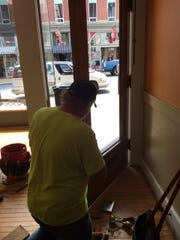 Hans Niederhauser repairs the door where a deer jumped through Thursday morning at the downtown North Main Street shop called The 'Field Market.