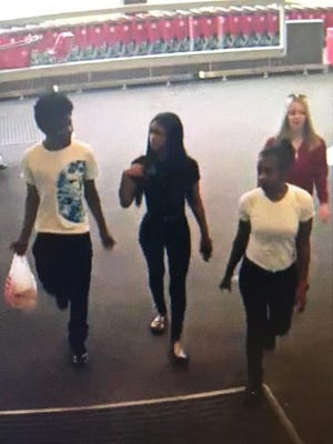 The man in the white tee shirt (far left) is being sought for shoplifting $6,000 worth of gift cards from the Bloomfield Township Target store.