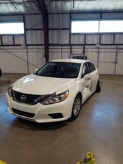 A white Nissan Altima was stolen from the slain couple's
