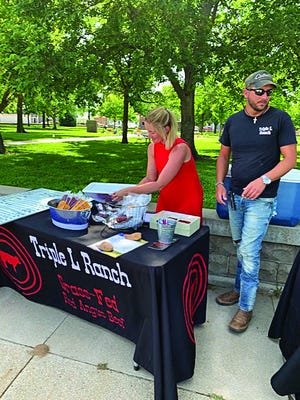 New vendors at the St. John Farmers' Market, Rhett and Sara Lambert of Lake City, present a tasting-table for shoppers to  sample their wares of grass-fed Red Angus beef, which is sold frozen in a variety of cuts. The weekly open-air market is held Thursdays from 4 to 5 p.m. on the east side of the park square in St.John.