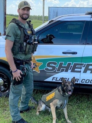 FCSO K-9 Axle poses in his new vest with his handler, Dep. Beausoleil.