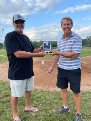 Larry Moklestad receives a plaque following his final home athletic contest of his tenure at ADM High School. PHOTO COURTESY OF ADM ATHLETICS