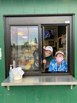 Sunshine Scott and Kristina Chapman poke their heads out of the new service window at Billy's Ice Cream Store in Adel. CONTRIBUTED PHOTOS