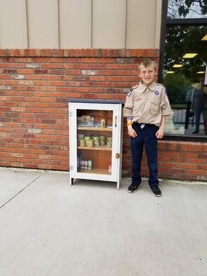 Josh Anderson, who is a member of the Boy Scout Troop 128, stands beside the new pantry outside of Colo Public Library. Photo courtesy of Colo Public Library