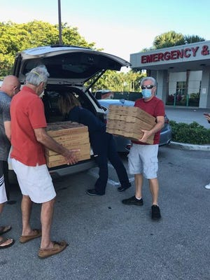 Valencia Bay residents deliver pizza to Delray Medical Center.
