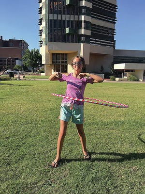 Raven Lemen tries her hand at hoola-hooping Friday evening during the Bartlesville library event. KRIS DUDLEY/EXAMINER-ENTERPRISE