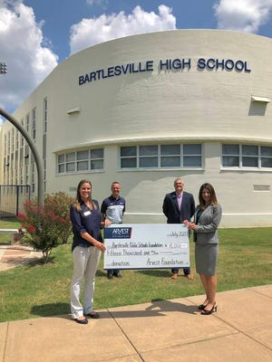 Arvest Bank president Kim Adams, right, presents a donation to Blair Ellis, executive director of BPSF, to help with coronavirus safety and the district's new agriculture program. Superintendent Chuck McCauley, back left, and Arvest community and business relations advisor Chris Batchelder, also attended the presentation. Courtesy.