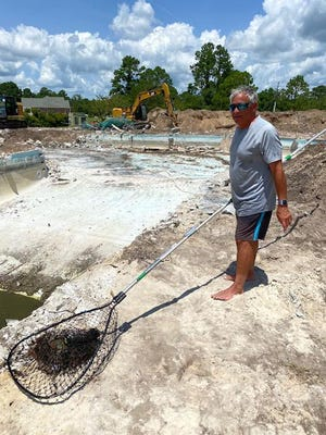 Gary Galante successfully captured this large turtle out of the mucky water before the old pool was demolished.