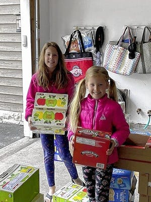 Kayla (left) and Lexi Hottel help prepare snack supplies the nonprofit Dublin Neighborhood Bridges organization packs into snacks bags for Dublin City Schools' students to pickup when they get their grab-and-go meals at one of the school district's distribution locations.