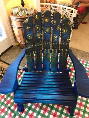 Aimee Hawkins paints a night scene on an Adirondack chair.