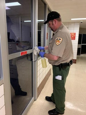 Grayson County Detention Officer Clint Thomas cleans inside the jail file photo from March.
