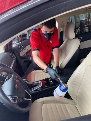 A Phil Long Dealerships worker sanitizes a vehicle interiors with DrivePur, an antibacterial, organically based and environmentally friendly purification treatment.