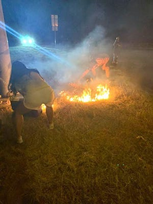 A citizen submitted this photo that depicts civilians who put out a grass fire Friday night at the corner of the Access Road and Austin Avenue. The citizen explained that Kelcy Sliger Potts and Esmeralda Soto, along with their children, stopped to help put out the fire. Soto said the group was driving back from Waco when they passed the fire. Soto called 9-1-1 to report the fire, and the group joined a couple of teens in pouring water from beverage containers onto the fire. The fire went out when Soto dragged a cooler across the flames, smothering them. The fire department arrived and saturdated the grass with water. Soto is pictured as she prepares to drag the cooler across the flames.
