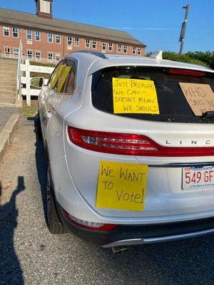 Several people protested Tuesday night outside Nipmuc Regional High School, where Upton's annual Town Meeting was held.