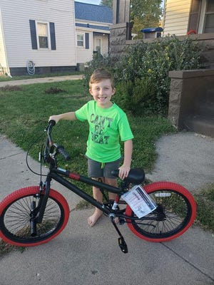 Cade Cox, 7, of Pekin, admires the new bicycle given to him by David Huskisson of Pekin to replace the one that disappeared from the front porch of his home last week.