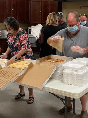 Patti Storer, left and Tim Cleeson, right, help prepare boxes of food for Sunday's free meal program at Open Arms Christian Church.