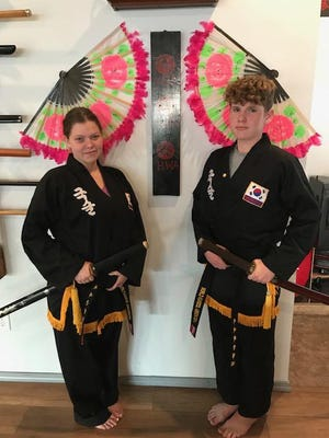 Kelsea Shughart (left) and Ty Corsaro, both of the Kuk Sool Won in Monmouth, received their black belts on July 25.