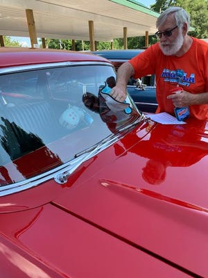 Sturgis resident Steve Ellington cleans the windshield of his 1957 Chevrolet Bel Air at Friday's fifth-annual Mendon Downtown Cruise-In.